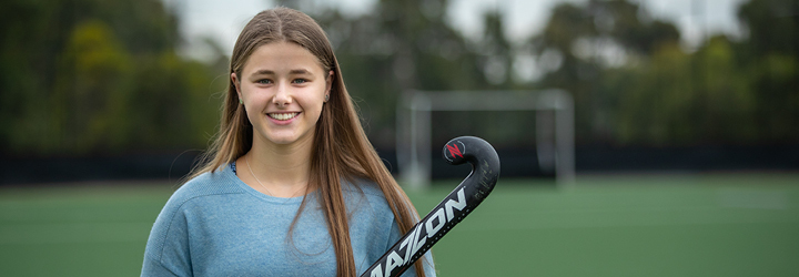 a girl stands on a hockey field holding her hockey stick and smiling
