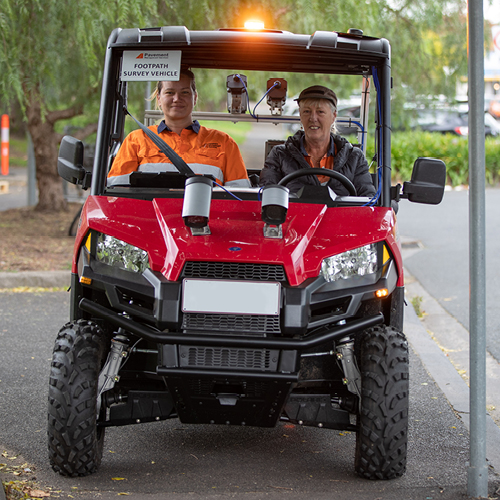 Two council workers on a quad bike completing a footpath condition audit.