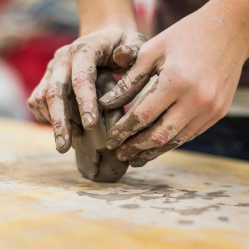A pair of hands sculpting a small block of clay
