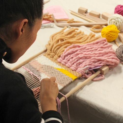 A person weaving at a table surrounded by balls of yarn