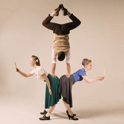 A man does a handstand on the lower backs of two standing women