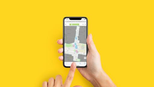 A pair of hands holds a mobile phone with a map on the screen